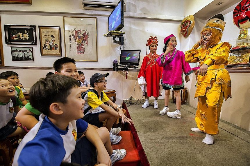 Primary 5 pupils from River Valley Primary School watching the Monkey God and other characters, played by schoolmates (from far left) Cayden Cheong, Chua Huiting and Sherwin Leow, in a Chinese opera. The event, to help pupils from selected schools le
