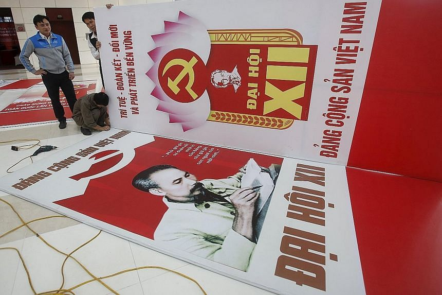 Workers putting the finishing touches yesterday to posters bearing the Communist Party logo and images of late Vietnamese revolutionary leader Ho Chi Minh. Vietnam's Communist Party holds its 12th five-yearly national congress in Hanoi tomorrow.
