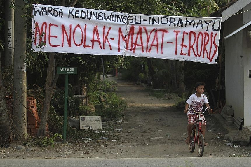 """A banner that reads """"Reject Terrorist's Body"""" hanging over the entrance to Kedungwungu, home village of Ahmad Muhazin, one of the militants involved in last Thursday's terror attack in Jakarta."""