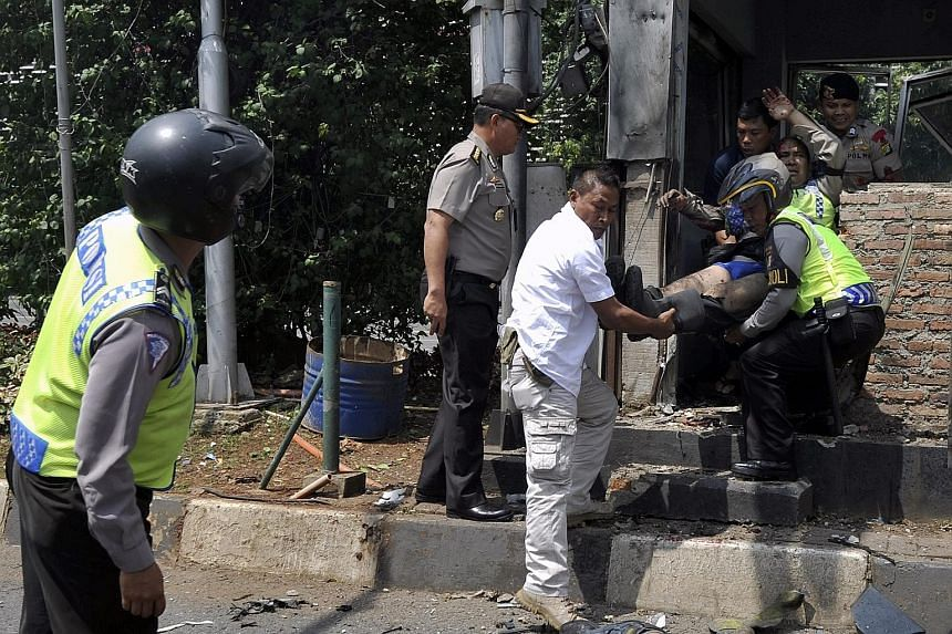 Indonesian police officers including Lt-Col Untung Sangaji (in white) evacuating an injured policeman after a bomb blast at a police post in front of a mall in Jakarta last Thursday. Lt-Col Untung told reporters yesterday he had no choice but to gun
