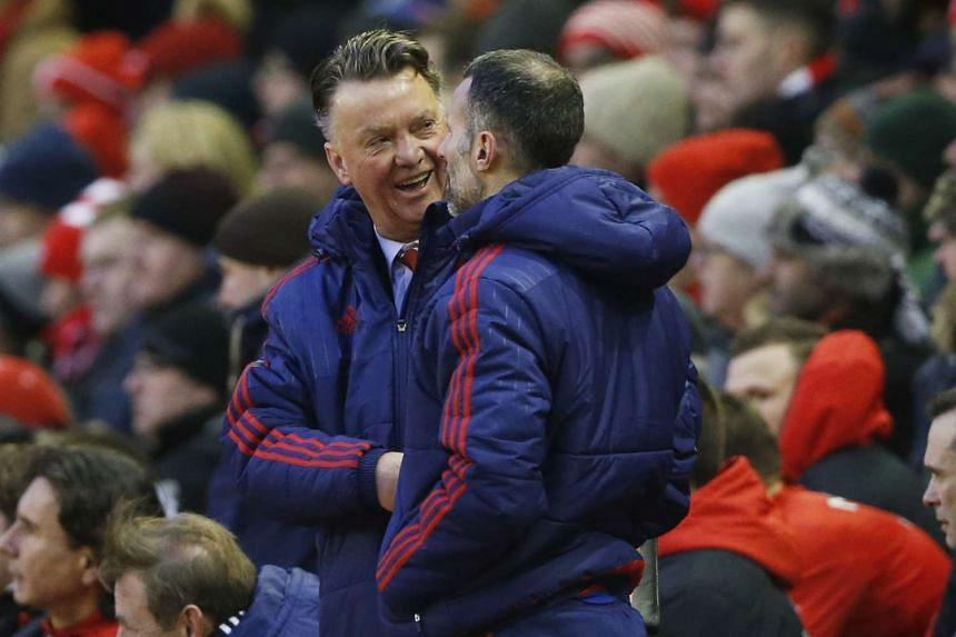 Manchester United's manager Louis van Gaal (left) shakes hands with assistant manager Ryan Giggs as they celebrate at full time.