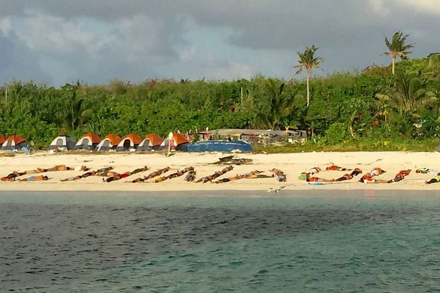 Filipino children forming a sign 'China Out' during a protest on a beach at Pag-asa island, a remote Philippine-held island in the South China Sea.