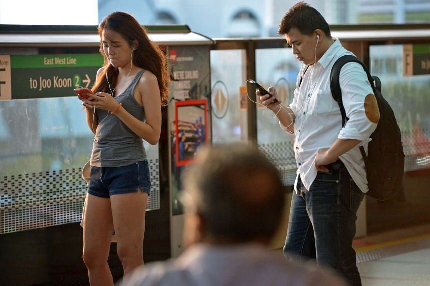 A file picture of mobile phone users in Singapore. PHOTO: SPH