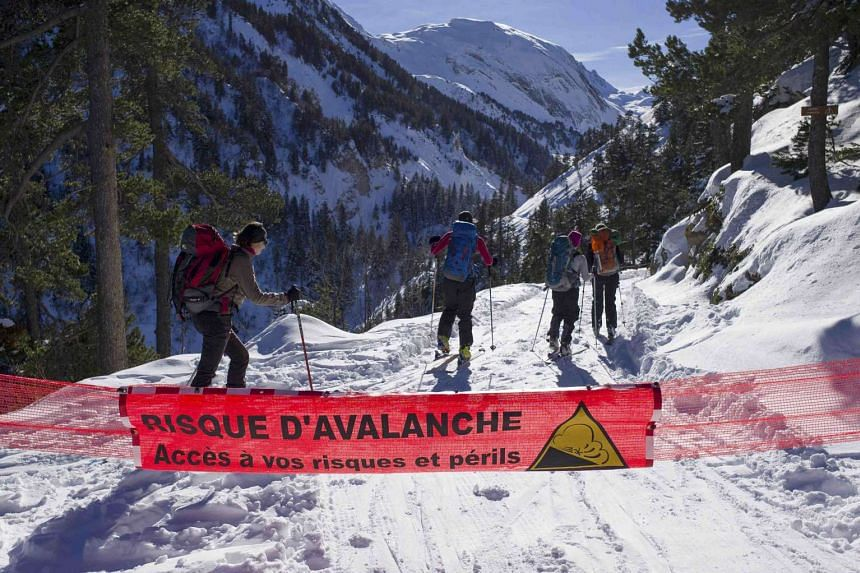 """A banner with the warning message, """"Risk of Avalanche - Proceed at your own risk and peril"""" stretches across a ski trail  in Courcheval, France."""