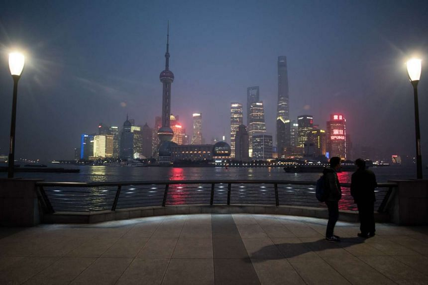 Two men stand at the bund near the Huangpu river across the Pudong New Financial district, in Shanghai on Monday, Jan 18.
