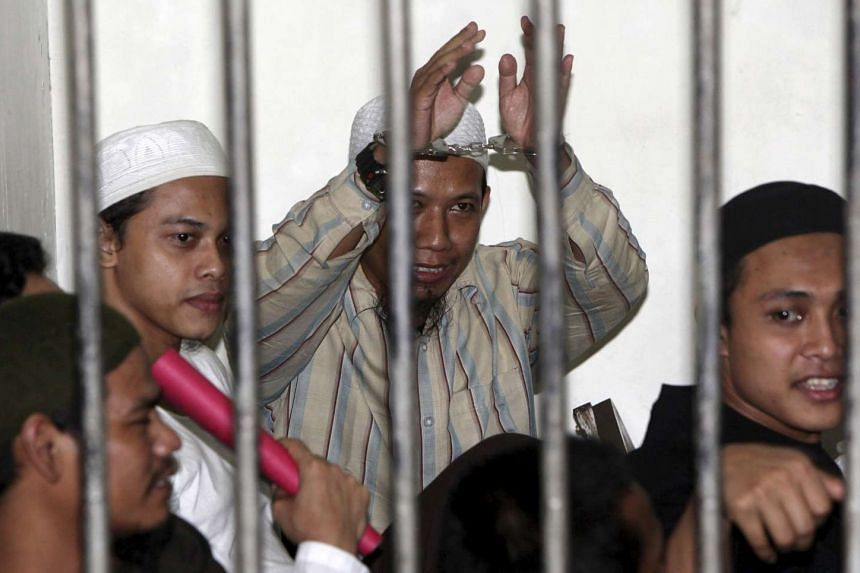 Radical Muslim cleric Aman Abdurrahman (centre), also known as Oman Rochman, raises his hands in a holding cell as he waits with other militants for their trial in Jakarta in an Aug 26, 2010 photo.