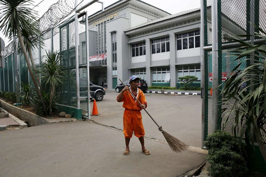 A worker sweeps a street at the gate of Cipinang prison in Jakarta on Sunday, Jan 17.