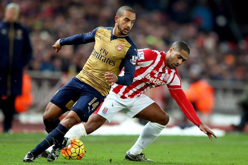 Arsenal's Theo Walcott (left) challenged by Stoke City's Glen Johnson during the English Premier League in Stoke, Britain, on Jan 17, 2016.