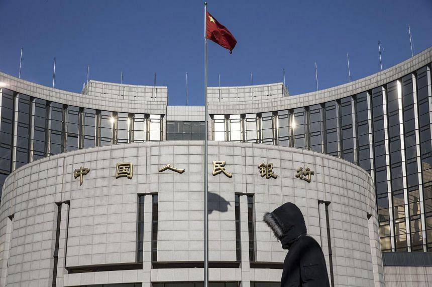 A pedestrian walking past the People's Bank of China headquarters in Beijing on Jan 18, 2016.