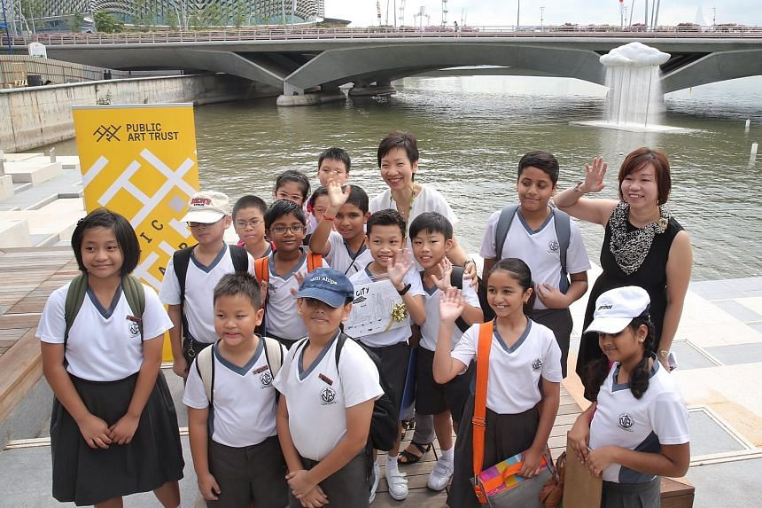 Minister for Culture, Community and Youth Grace Fu has a photograph taken with pupils from Naval Base Primary School in front of Cloud Nine: Raining by artist Tan Wee Lit.