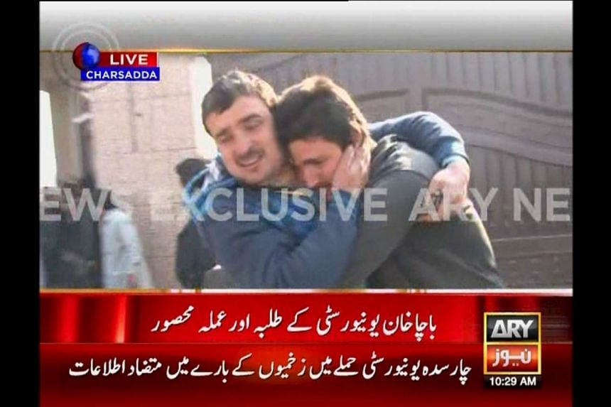 Two men consoling each other as people are evacuated at the Bacha Khan University during an attack by militants, in this video still released by ARY News on Jan 20.