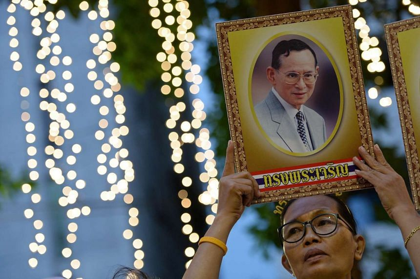 A Thai well-wisher holds a portrait of King Bhumibol Adulyadej as people gather to celebrate his 88th birthday.