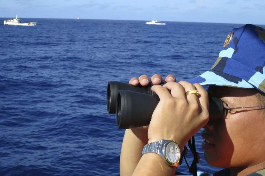 A crewman from the Vietnamese coastguard ship 8003 looks out at sea.