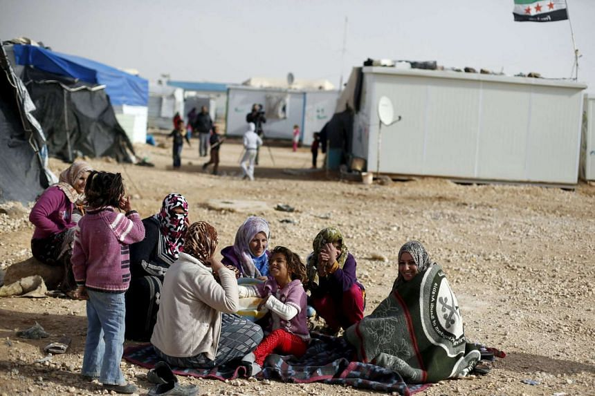 Syrian refugees sit in front of their tents at the Al Zaatri refugee camp in Mafraq, Jordan.