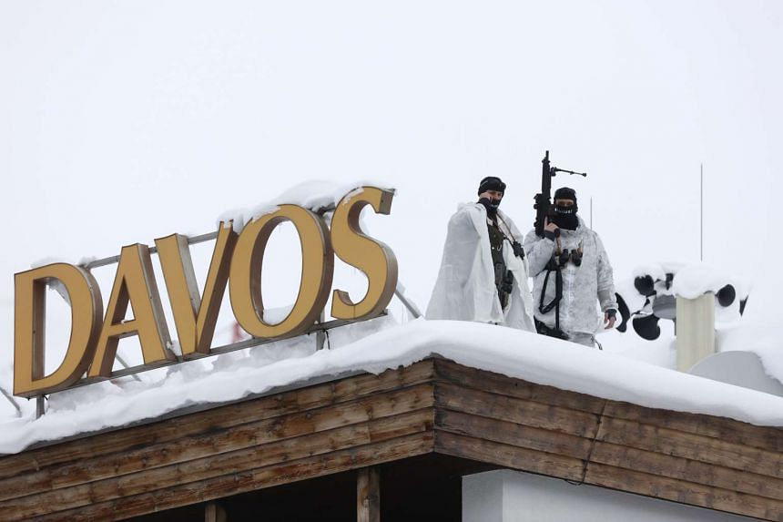 Armed members of the Swiss Police watching from the roof of the Hotel Davos ahead of the World Economic Forum.