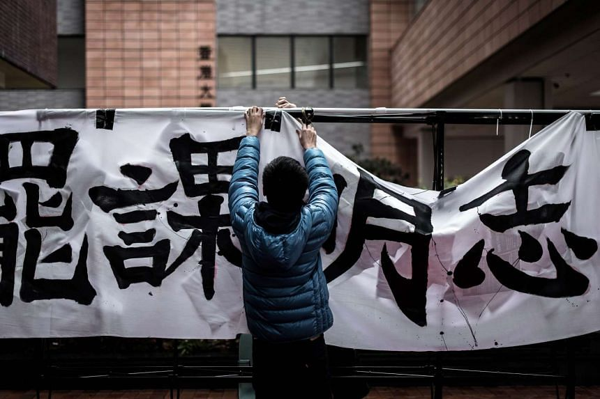 A student sets up a banner during a protest at Hong Kong University on Jan 20, 2016.