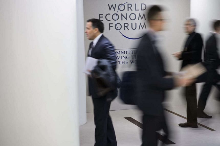 People walk past a logo during the first day of the 46th Annual Meeting of the World Economic Forum, WEF, in Davos.