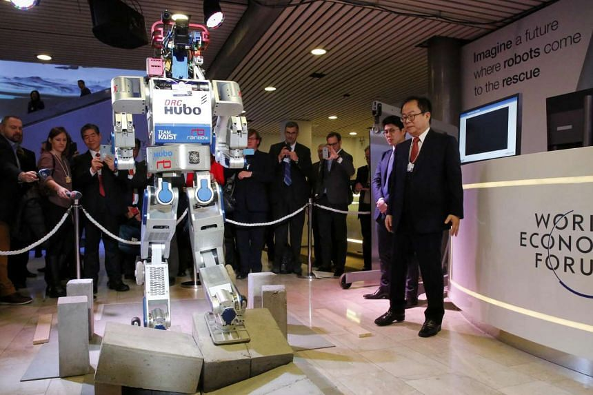 HUBO, a multifunctional walking humanoid robot performs a demonstration of its capacities next to its developer Oh Jun Ho.