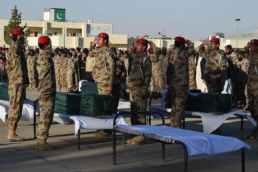 Pakistani paramilitary soldiers saluting the coffins of their colleagues during a funeral ceremony in the city of Quetta on Monday. At least six paramilitary soldiers were killed when their vehicle hit a roadside bomb in Pakistan's south-western prov