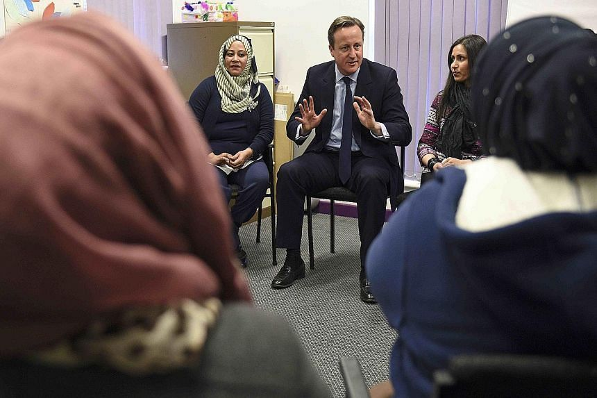 Britain's Prime Minister David Cameron speaking with women attending an English language class. He announced on Monday that Muslim women who fail to learn good English could face deportation from Britain.