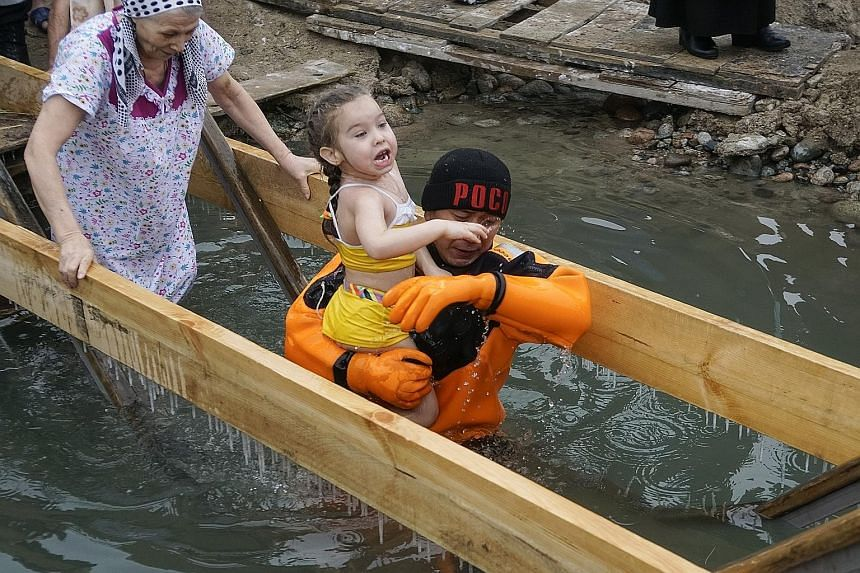 An emergency rescuer carrying a child who was bathing in freezing waters during the Epiphany celebration at the Bolshaya Almatinka river bank in Almaty, Kazakhstan, yesterday. Marking the baptism of Jesus according to the Julian calendar, the Orthodo