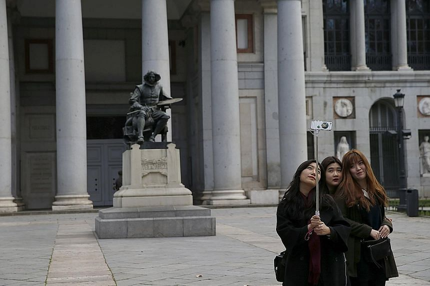 Tourists taking a wefie in front of a statue of Spanish painter Diego Velazquez outside the Prado Museum in Madrid. The number of international tourists rose by 4.4 per cent worldwide last year to hit a record 1.18 billion despite concerns over extre