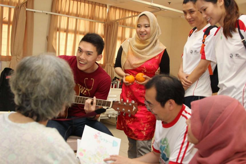 NUS medical student Mr Ong Jing Zhi, 21, singing with National Healthcare Group (NHG) staff to a resident from the Society for the Aged Sick.