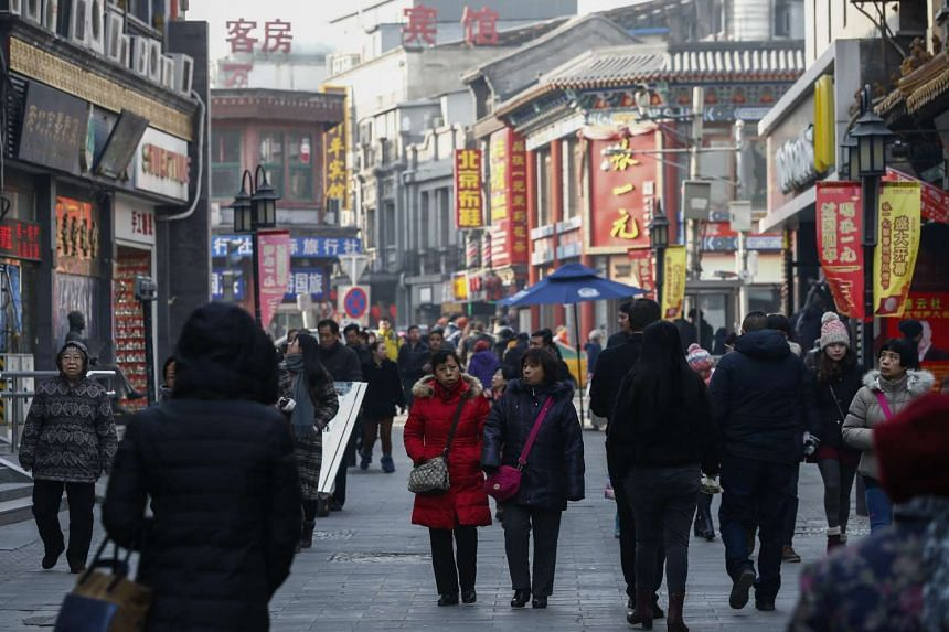 Citizens walk past commercial establishments at the shopping area of Qianmen district in Beijing, China, Jan 19, 2016.