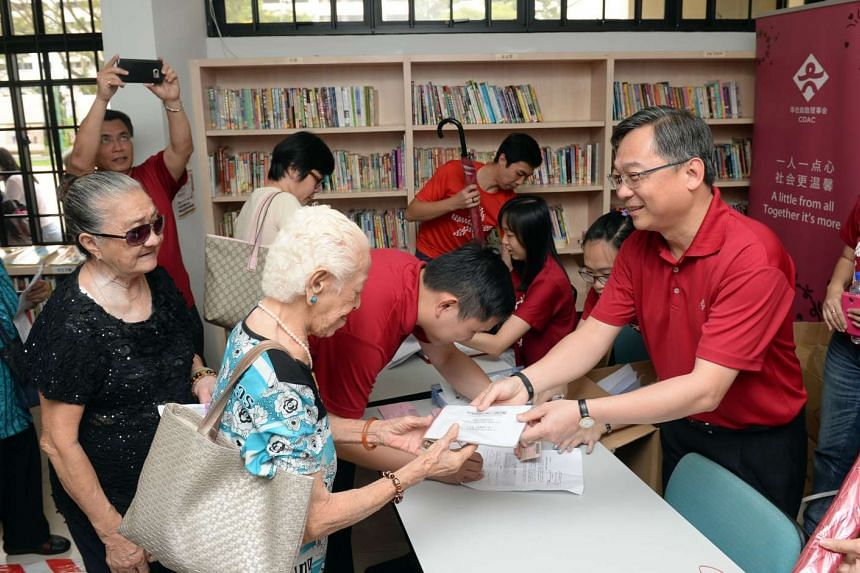 Minister for Health Gan Kim Yong presenting Jubilee packs to low-income residents at CDAC@Bukit Panjang on Dec 27, 2015.