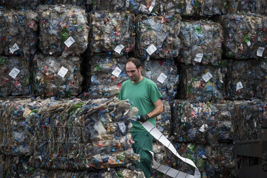 A processing plant employee works near stacks of plastic waste collected from the sea by fishermen in Spain.
