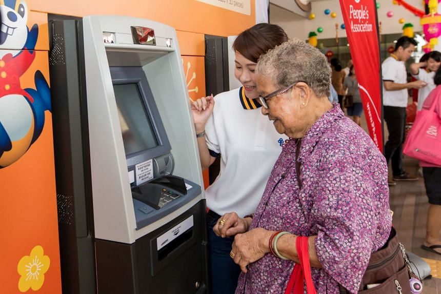 People lining up to use the pop-up ATMs at Ci Yuan Community Club at Hougang Avenue 9.