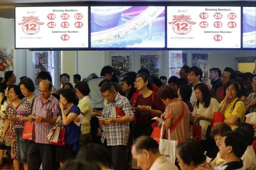 Punters checking their tickets at the draw at the main Singapore Pools branch in Middle Road for the Toto Hongbao draw on Feb 27, 2015.