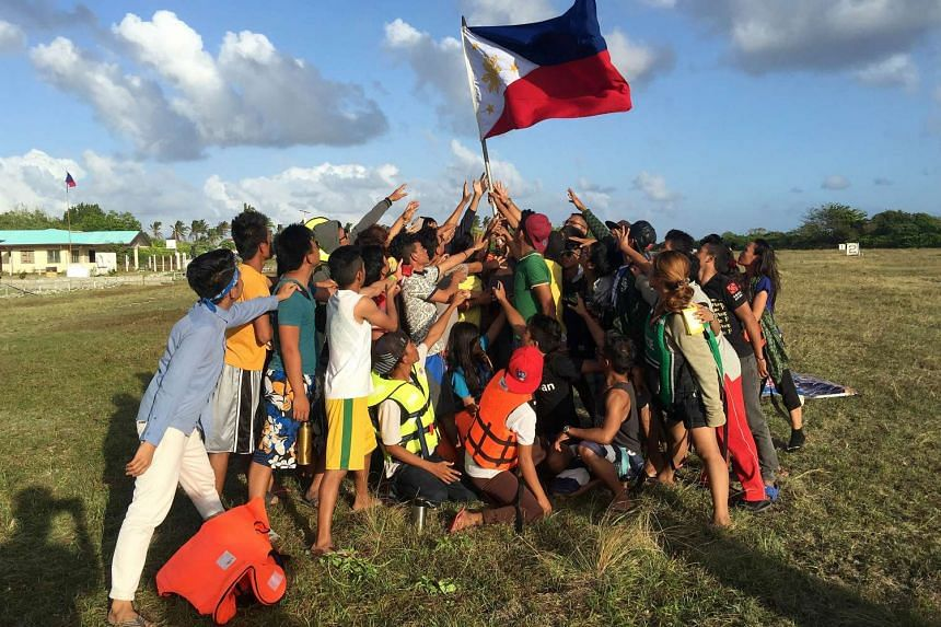 Filipino children holding up a national flag during a protest at Pagasa island in the South China Sea.