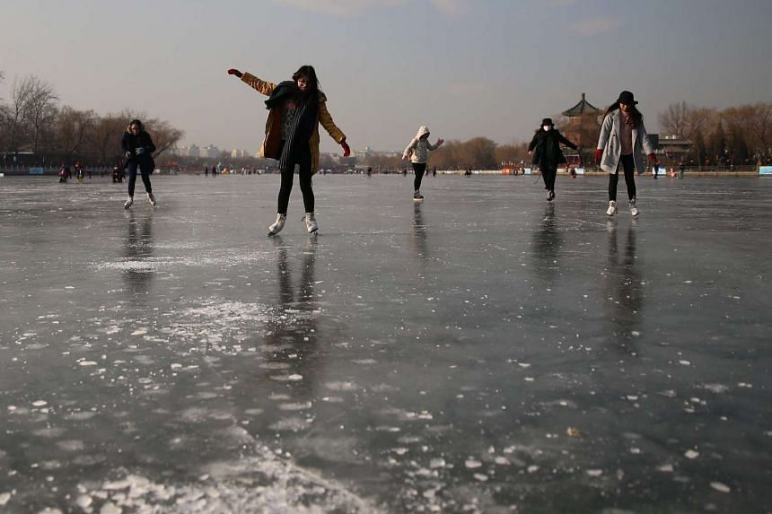 Chinese people skate on the frozen surface of Houhai Lake in Beijing, China.