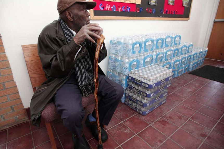 A man sitting next to a stack of bottled water at a church in Flint, Michigan, on Jan 17.