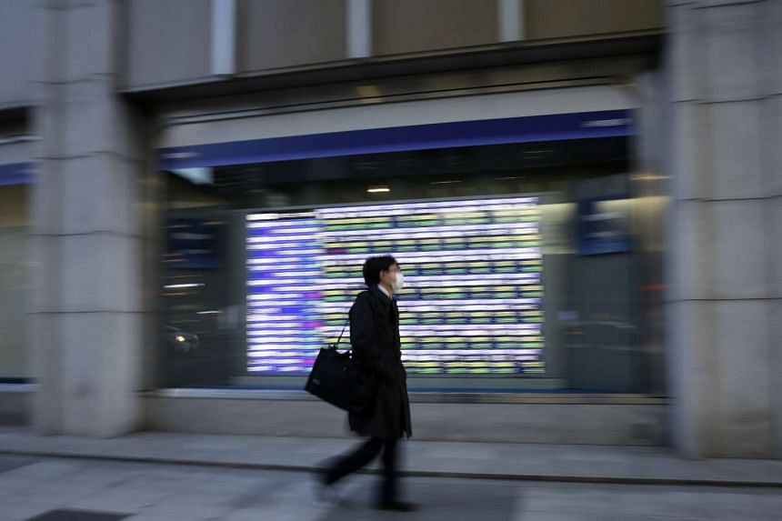 A pedestrian walks past an electronic stock board outside a securities firm in Tokyo, Japan, on Jan 20, 2016.
