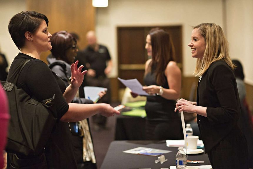 Job-seekers speaking with company representatives at a career fair in Chicago on Jan 14, 2016.