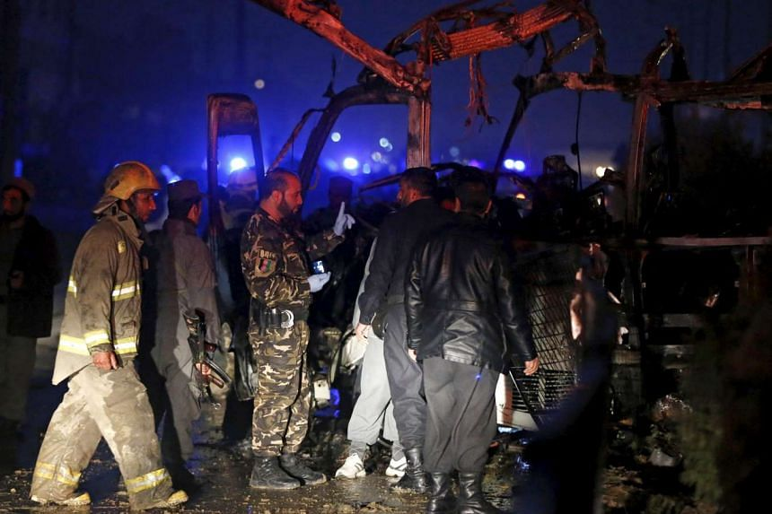 Afghan policemen and firefighters inspecting the wreckage of a bus that was hit by a suicide bomb attack in Kabul on Jan 20, 2016.