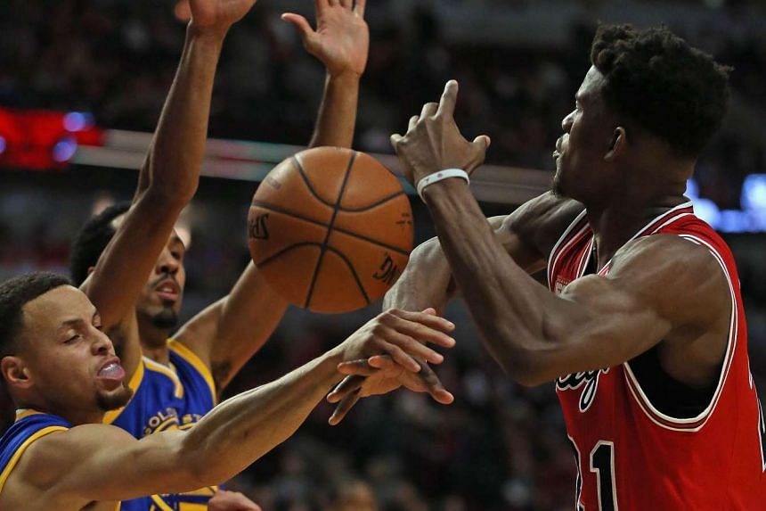 Stephen Curry (left) of the Golden State Warriors knocks the ball away from Jimmy Butler of the Chicago Bulls at the United Center on Jan 20, 2016.