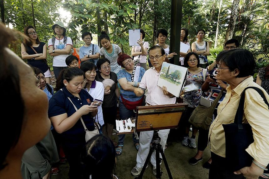 Mr Tham Pui San holding up a painting (left photo) and surrounded by participants (right photo) at the Singapore Botanic Gardens. The free sessions last two or three hours.
