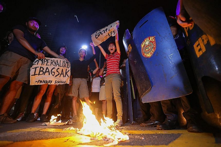 Students burning a mock American flag outside the US Embassy in Manila yesterday during a rally against the US-Philippine Enhanced Defence Cooperation Agreement. The pact allowing an increased presence of US military forces for training in the Philip