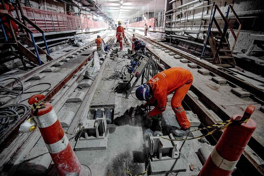 Workers on duty at part of Line 4, which is still being built. It will reach the Western part of Rio, where the Olympic Village and many of the competitions are based. Works are 83 per cent complete.
