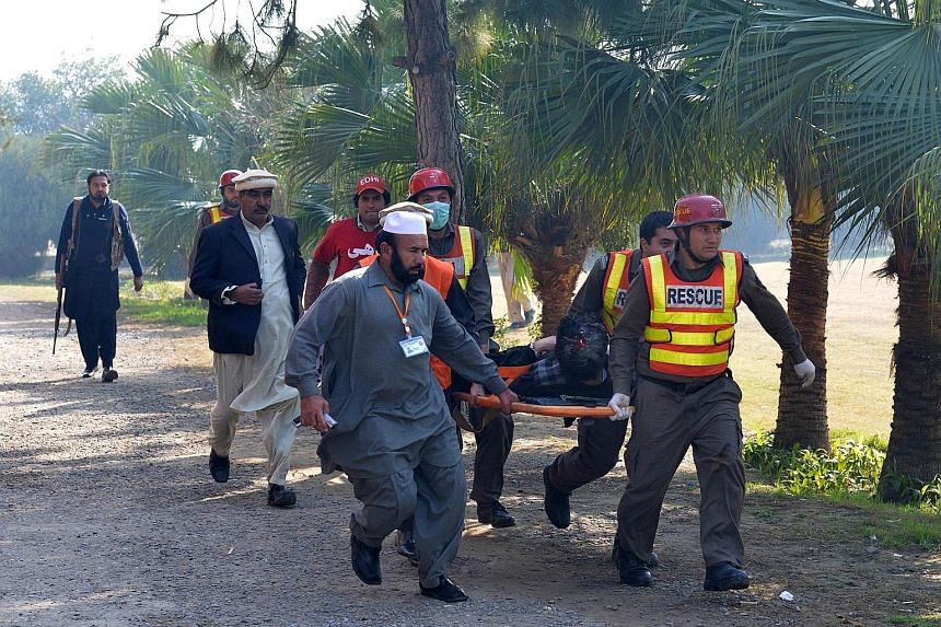 Students fleeing Bacha Khan University in Charsadda (above) following an attack by militants yesterday, while army soldiers rescue a victim (left).