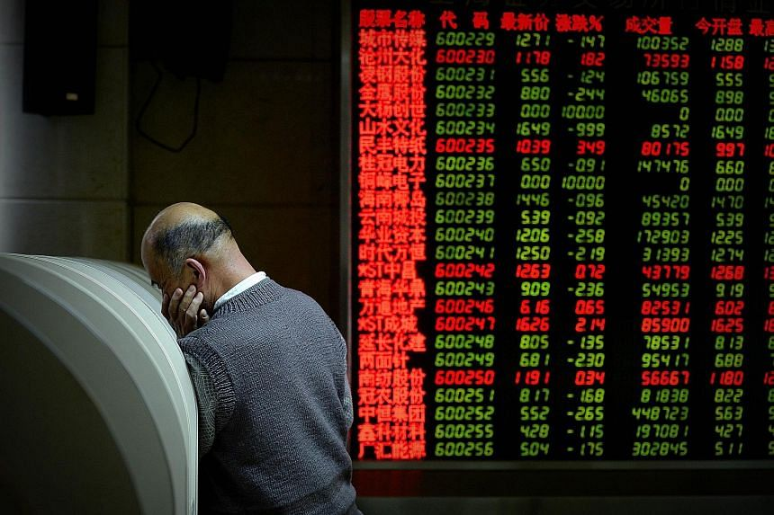 A man using a computer terminal to check stock prices at a securities firm in Beijing.