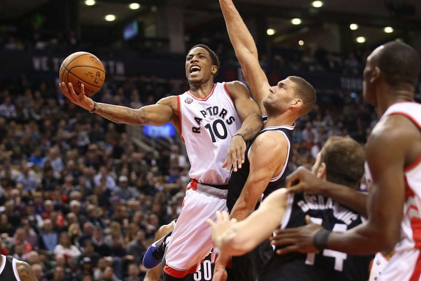 Toronto Raptors guard DeMar DeRozan (10) is fouled on his way to the basket by Brooklyn Nets center Brook Lopez (11) at Air Canada Centre.