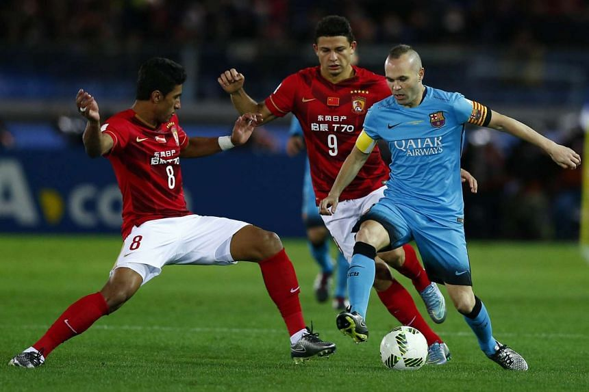 Guangzhou Evergrande's Elkeson (centre) and Paulinho (left) battling with Barcelona's Andres Iniesta during their Club World Cup match in Yokohama on Dec 17, 2015.