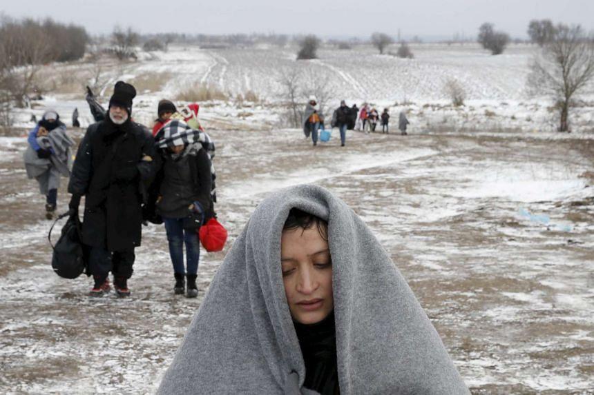 Migrants walking through a frozen field after crossing the border from Macedonia, near the village of Miratovac, Serbia, on Jan 18, 2016.