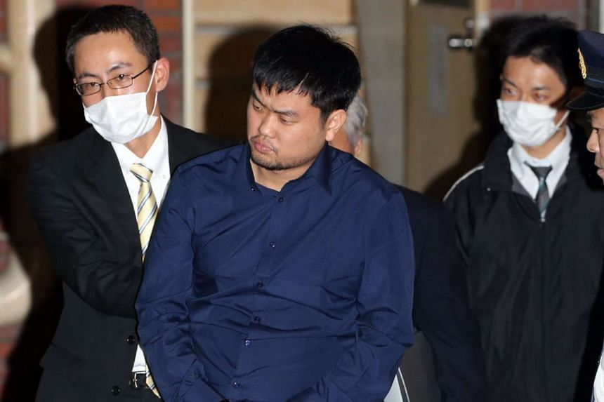 Jeon Chang Han (centre) is escorted out of a police station in Tokyo on Dec 9, 2015.