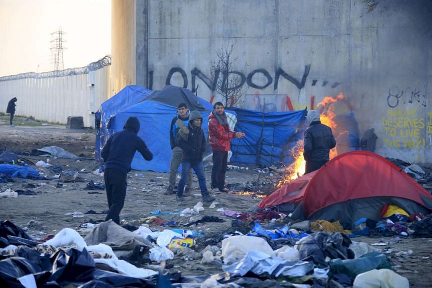 """Migrants warm their hands near a wood fire in a dismantled area of the Calais camp known as """"The Jungle""""."""