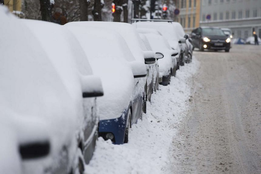 Snow covers cars parked along a street in Oslo in December.